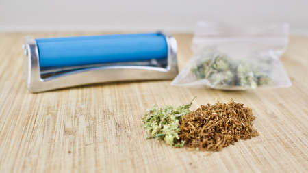 Blue rolling machine, bag with weed, and marijuana on wooden desk. Stock Photo
