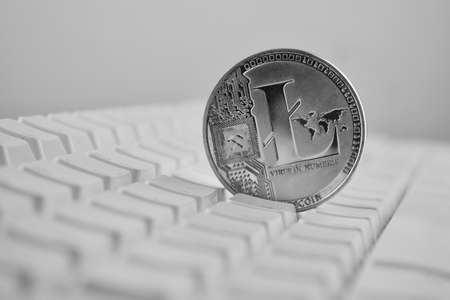 Digital currency physical silver Litecoin coin on white computer keyboard.