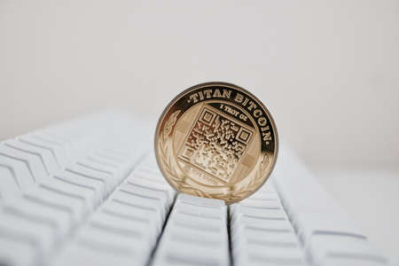 Digital currency physical gold bitcoin coin on white computer keyboard.