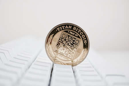Digital currency physical gold titan bitcoin coin on white computer keyboard.