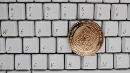 Digital currency physical gold titan bitcoin on white computer keyboard.