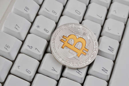 Digital currency physical silver bitcoin coin on white keyboard. Yellow Sign.