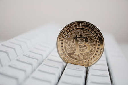 Cryptocurrency physical gold bitcoin coin on white computer keyboard.