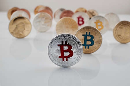 Digital currency physical red bitcoin coin near other bitcoins.