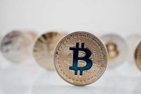 Cryptocurrency physical gold bitcoin coin with blue sign.