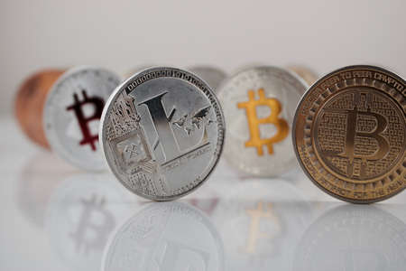 Digital currency physical silver Litecoin coin near gold and silver bitcoins.