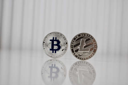 Digital currency physical silver bitcoin and litecoin coins on white table.