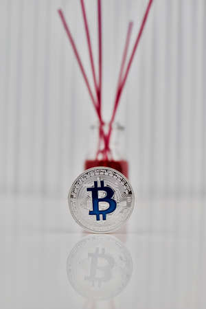 Digital currency physical silver bitcoin coin with blue sign near fragrance.