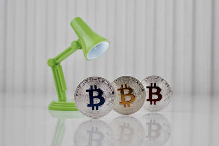 Cryptocurrency physical silver blue yellow and red bitcoin coin on white table near green lamp.