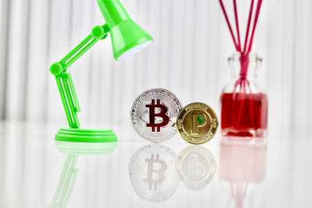 Digital currency physical silver bitcoin and gold peercoin coin near lamp