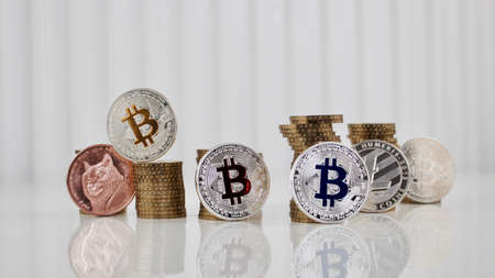 Digital currency physical bitcoins, dogecoin, litecoin and gold money on the white table. Money concept.
