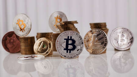 Digital currency physical silver bitcoin coin near gold money on the table. Stock Photo