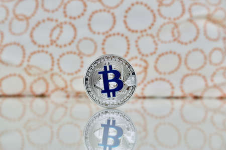 silver coins: Digital currency physical silver bitcoin coin with blue sign near circles. Stock Photo