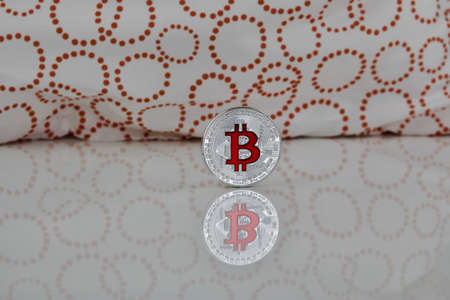 silver coins: Cryptocurrency physical silver bitcoin coin with red sign on the white and orange scene. Stock Photo