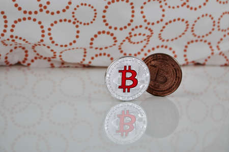 Cryptocurrency physical silver bitcoin coin and brass bitcoin on the white scene.
