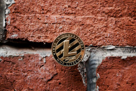 Digital currency physical gold litecoin coin on the brick wall. Stock Photo
