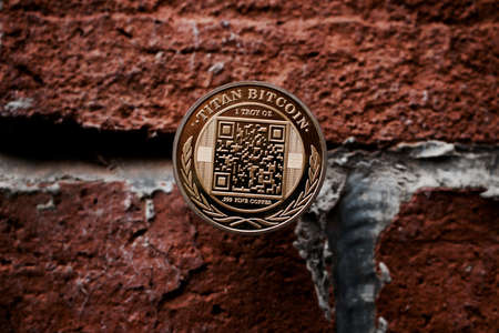 Cryptocurrency physical gold titan bitcoin coin on the brick wall. Stock fotó