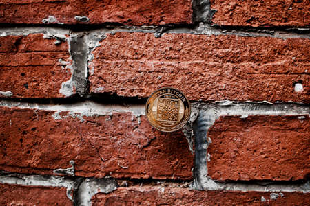 Digital currency physical gold titan bitcoin coin on the brick wall. Stock Photo