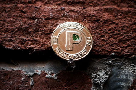 Cryptocurrency physical gold peercoin coin with green leaf in sign on black brick wall.