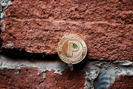 Digital currency physical gold peercoin coin with green leaf on the brick wall. Stock Photo