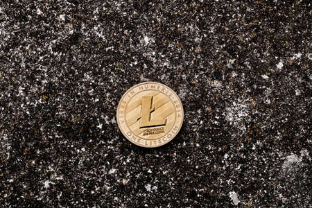 Cryptocurrency physical gold litecoin coin on black dark background.