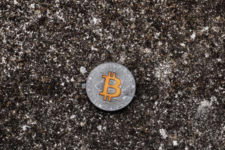 silver coins: Digital currency physical silver bitcoin coin with yellow sign on dark background.