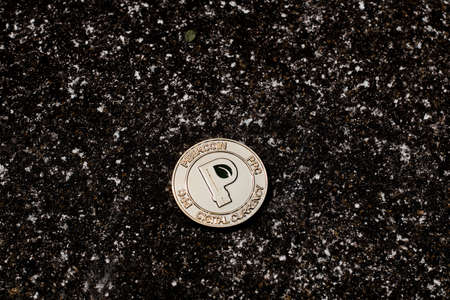 Digital currency physical gold peercoin coin on dark background.