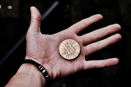Digital currency physical gold bitcoin coin in man hand with black bracelet.