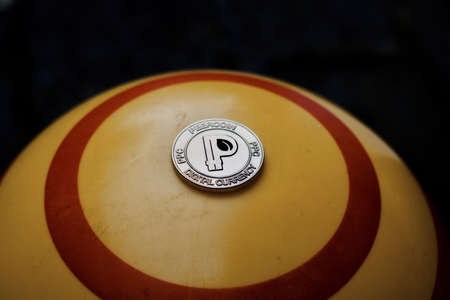 peer to peer: Digital currency physical gold peercoin coin on yellow circle background. Foto de archivo