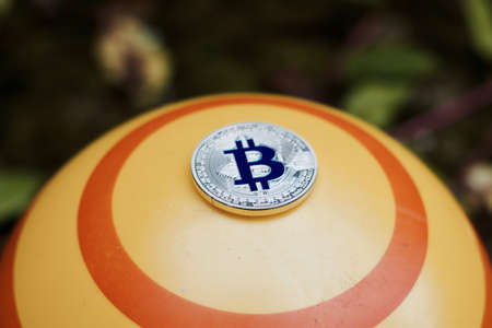Digital currency physical blue bitcoin coin on yellow circle background.