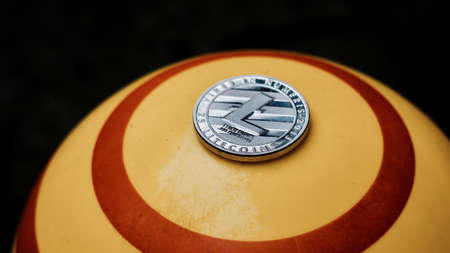 Digital currency physical silver litecoin coin on yellow circle background. Фото со стока