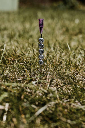 Small pins silver inscription on the needle in green grass. Outdoor natural concept.