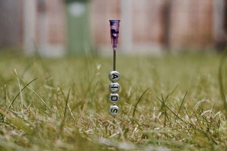Small silver pins letters on the needle. Green grass natural outdoor concept. Stock Photo