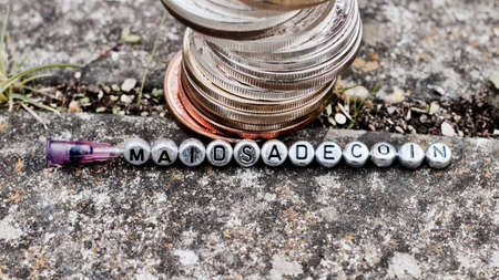 silver coins: Digital currency physical coins near silver small letters inscription MAIDSADECOIN. Stock Photo
