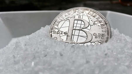 silver coins: Digital currency physical metal coin on the white cristal background. Virtual cash concept.