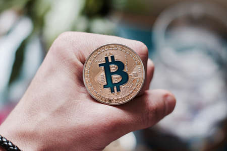 silver coins: Digital currency physical metal bitcoin coin on man hand. Virtual cash concept. Stock Photo