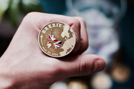 Europe leaving. Article 50 and brexit coin in man hand. Dark background.