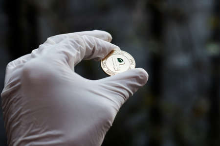 Digital currency physical gold peercoin coin in hand. White gloves concept. Stock Photo