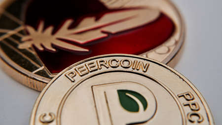 Digital currency physical gold peercoin coin near different currency. Virtual cash concept. Stock Photo