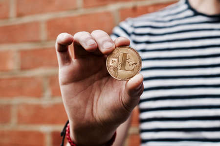 Digital currency physical gold litecoin coin in man hand near brick wall.