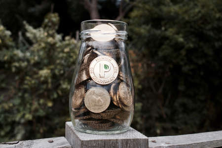 Digital currency physical gold peercoin coin with green sign. Transparent glass jar. Stock Photo