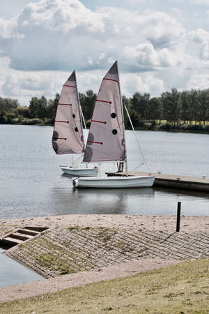 Two beautiful sailboats on the lake in Milton Keynes near pier. Bedfordshire.