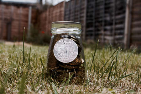 silver coins: Digital currency physical silver bitcoin coin in glass jar on grass in garden. Stock Photo