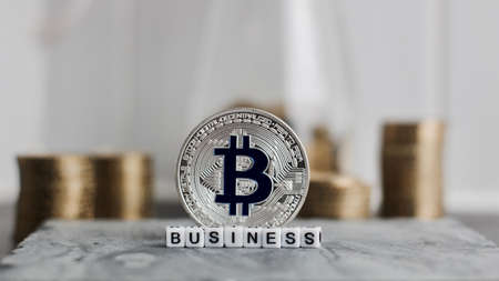 Digital currency physical metal bitcoin coin near business white letters inscription.