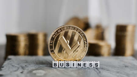 Digital currency physical metal litecoin coin near business white letters inscription.