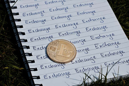 Digital currency physical metal litecoin coin on the notebook with exchange inscription. Green outdoor concept.