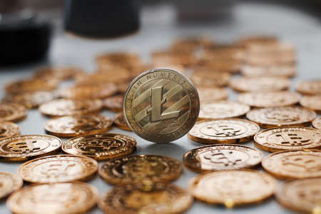 Digital currency physical metal litecoin coin on the gold bitcoins. Gold money concept. Stock Photo