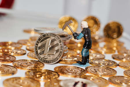 Digital currency physical metal Litecoin gold coin. Man mining bitcoins. Gold coins. Stock Photo