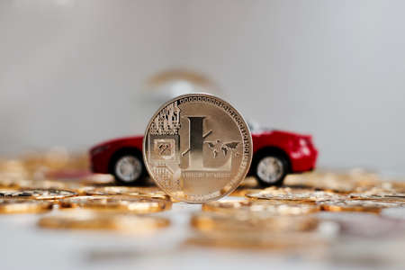 Digital currency physical metal litecoin coin near red luxury car. Finance cryptocurrency concept.