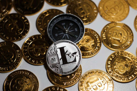 Cryptocurrency physical metal Litecoin coin on gold bitcoin coins near compass. Money concept.
